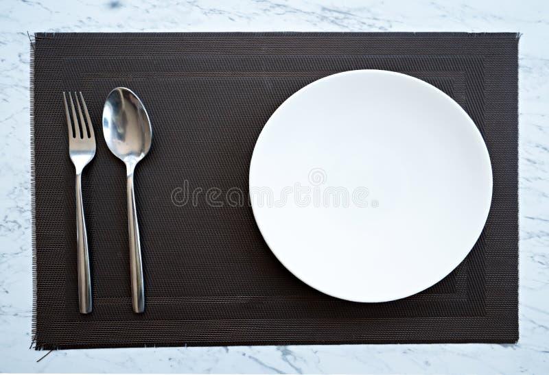 Πιάτο με ένα κουτάλι και δίκρανο στον πίνακα στοκ φωτογραφία με δικαίωμα ελεύθερης χρήσης