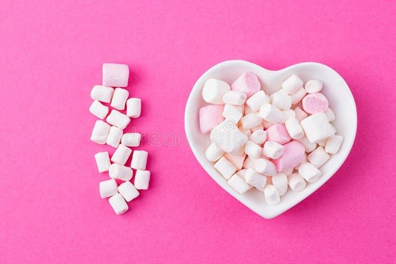 Πιάτο με μορφή της καρδιάς με marshmallow σε ένα ρόδινο υπόβαθρο στοκ φωτογραφία