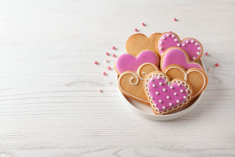 Πιάτο με τα διακοσμημένα διαμορφωμένα καρδιά μπισκότα στον ξύλινο πίνακα στοκ φωτογραφία