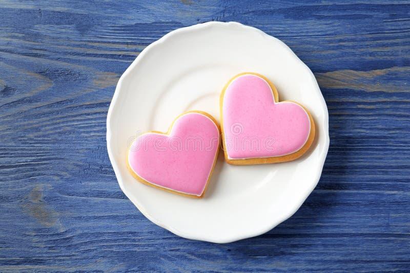 Πιάτο με τα διακοσμημένα διαμορφωμένα καρδιά μπισκότα στο ξύλινο υπόβαθρο στοκ εικόνα με δικαίωμα ελεύθερης χρήσης