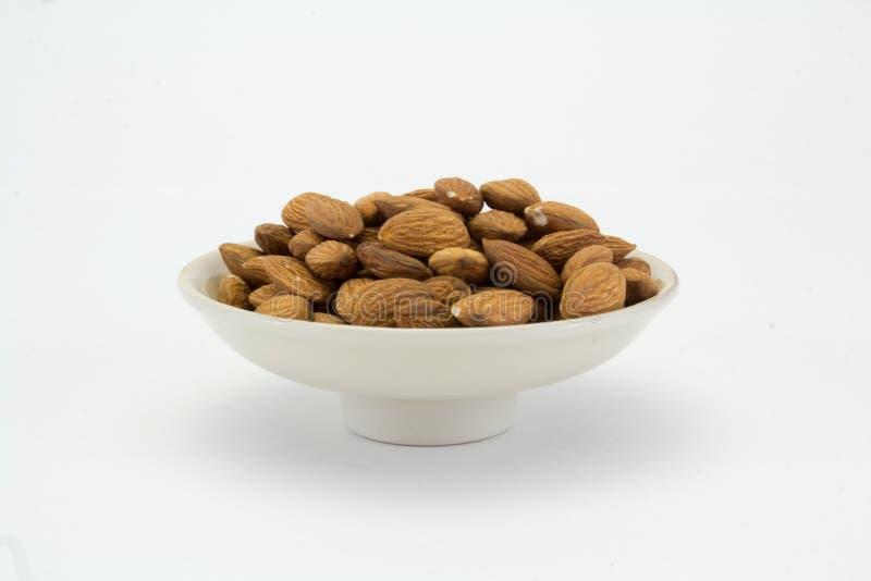 Πιάτο με τα καρύδια αμυγδάλων σε ένα άσπρο υπόβαθρο στοκ φωτογραφία με δικαίωμα ελεύθερης χρήσης