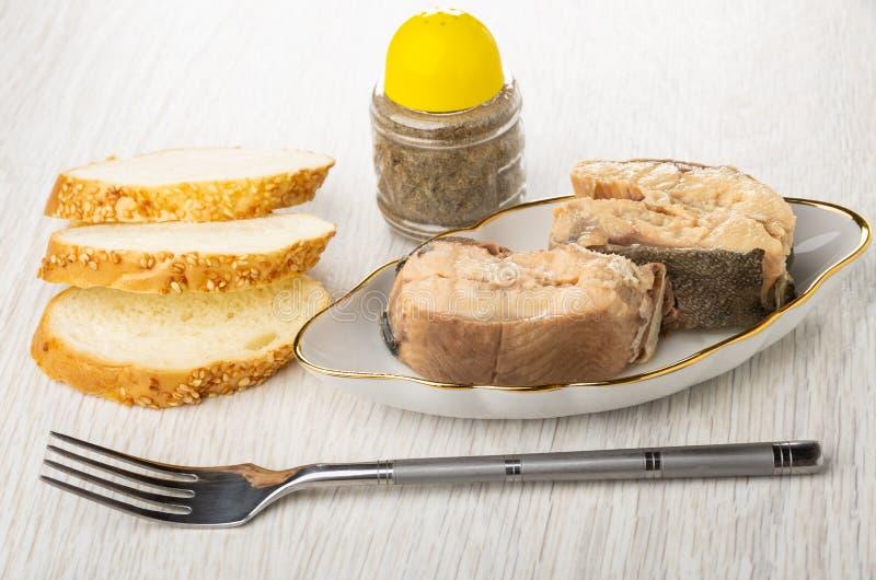 Πιάτο με τα κομμάτια του κονσερβοποιημένου ρόδινου σολομού, του δονητή πιπεριών, του ψωμιού και του δικράνου στον ξύλινο πίνακα στοκ εικόνες με δικαίωμα ελεύθερης χρήσης