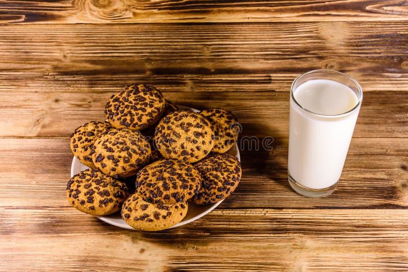 Πιάτο με τα μπισκότα τσιπ σοκολάτας και ένα ποτήρι του γάλακτος σε έναν ξύλινο πίνακα στοκ φωτογραφία με δικαίωμα ελεύθερης χρήσης