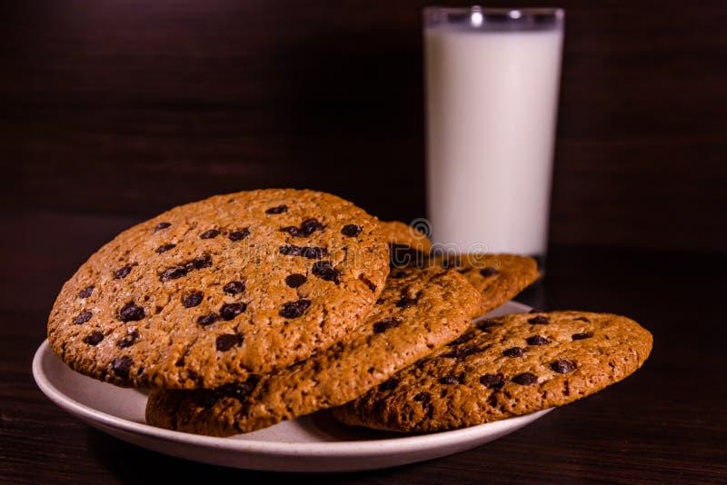 Πιάτο με τα μπισκότα τσιπ σοκολάτας και ένα ποτήρι του γάλακτος σε έναν σκοτεινό ξύλινο πίνακα στοκ εικόνα με δικαίωμα ελεύθερης χρήσης