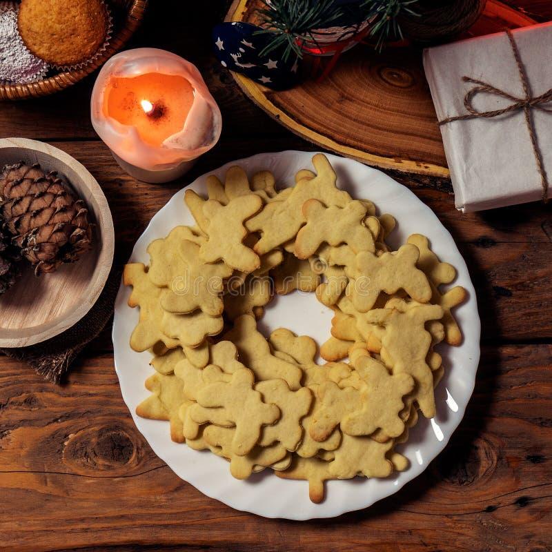 Πιάτο με τα νόστιμα μπισκότα, το κερί και το δώρο Χριστουγέννων στον ξύλινο πίνακα Τοπ όψη Τετράγωνο Instagram στοκ φωτογραφίες με δικαίωμα ελεύθερης χρήσης