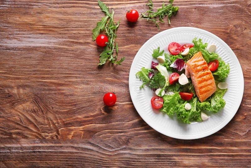 Πιάτο με τα νόστιμα ψημένα στη σχάρα ψάρια και φρέσκια σαλάτα στον ξύλινο πίνακα στοκ εικόνα