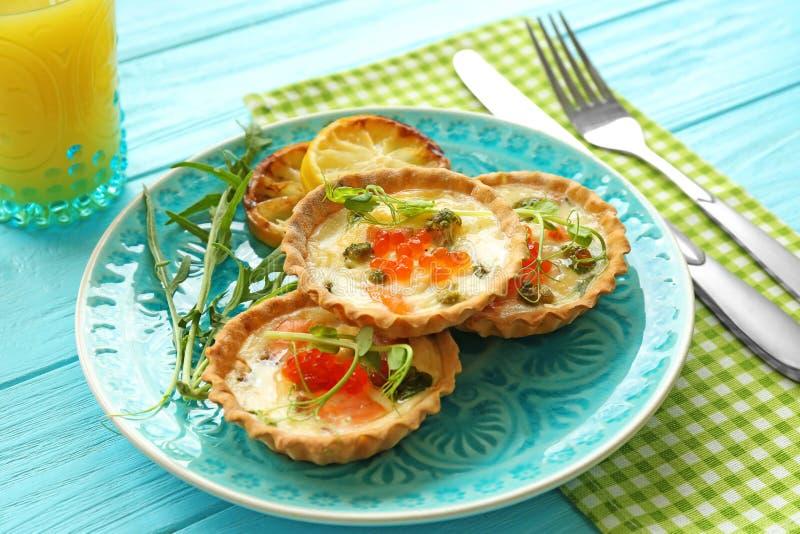 Πιάτο με τα νόστιμα tartlets σολομών στοκ φωτογραφίες