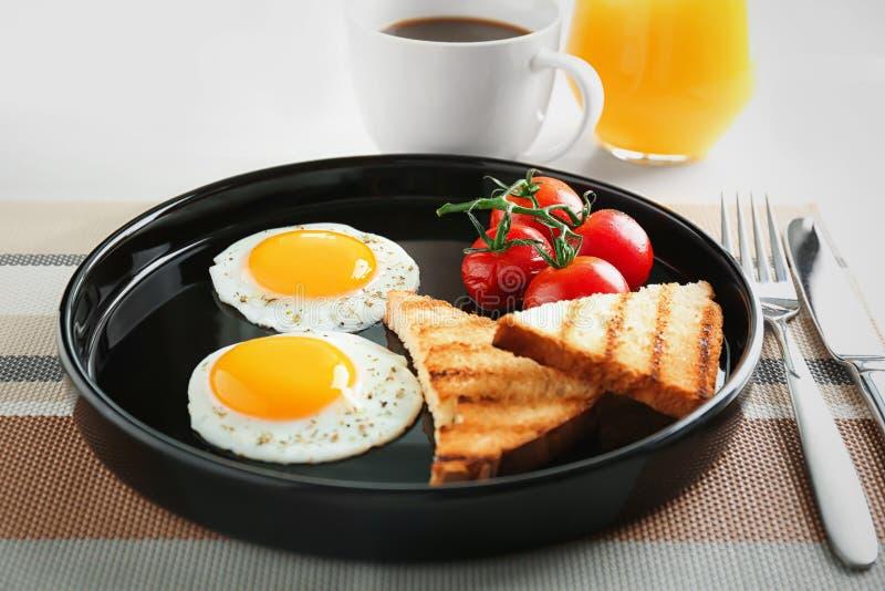 Πιάτο με τα τηγανισμένες αυγά, τις φρυγανιές και τις ντομάτες κερασιών στοκ φωτογραφίες με δικαίωμα ελεύθερης χρήσης