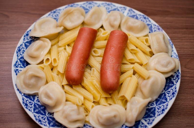Πιάτο με τα τρόφιμα, λουκάνικα, μπουλέττες, ζυμαρικά στοκ εικόνα