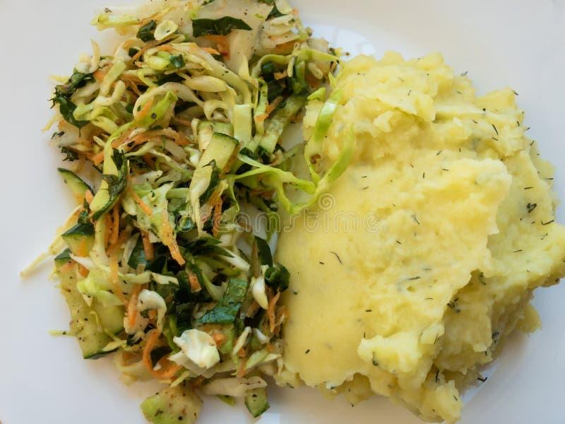 Πιάτο με την πολτοποίηση πατατών, σαλάτα λάχανων που αναμιγνύεται με τα καρότα και τα φύλλα πικραλίδων στοκ εικόνες