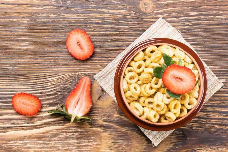 πιάτο με τις νιφάδες καλαμποκιού και φράουλα στον πίνακα στοκ φωτογραφίες