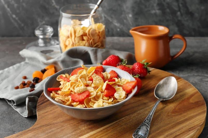Πιάτο με τις νόστιμες νιφάδες καλαμποκιού και φράουλα στον ξύλινο πίνακα στοκ φωτογραφία με δικαίωμα ελεύθερης χρήσης