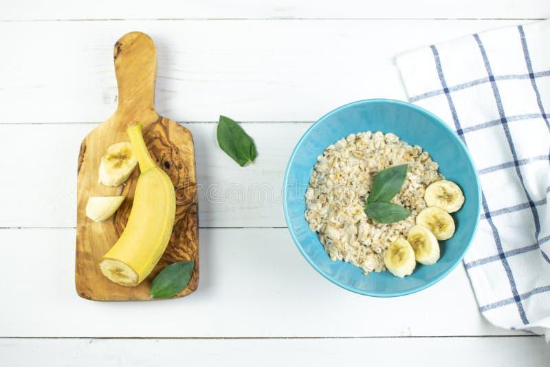 Πιάτο με τις νόστιμες oatmeal και μπανανών φέτες στο άσπρο ξύλινο υπόβαθρο Εικόνα έννοιας του προγεύματος, υγιής κατανάλωση στοκ εικόνα