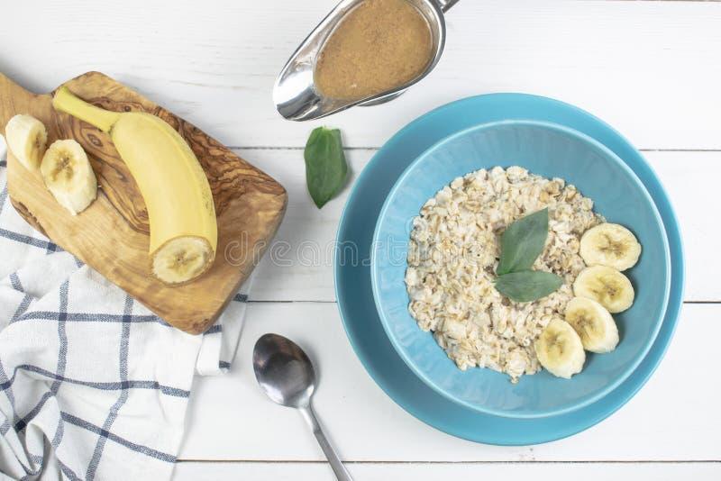 Πιάτο με τις νόστιμες oatmeal και μπανανών φέτες στο άσπρο ξύλινο υπόβαθρο Εικόνα έννοιας του προγεύματος, υγιής κατανάλωση στοκ φωτογραφία