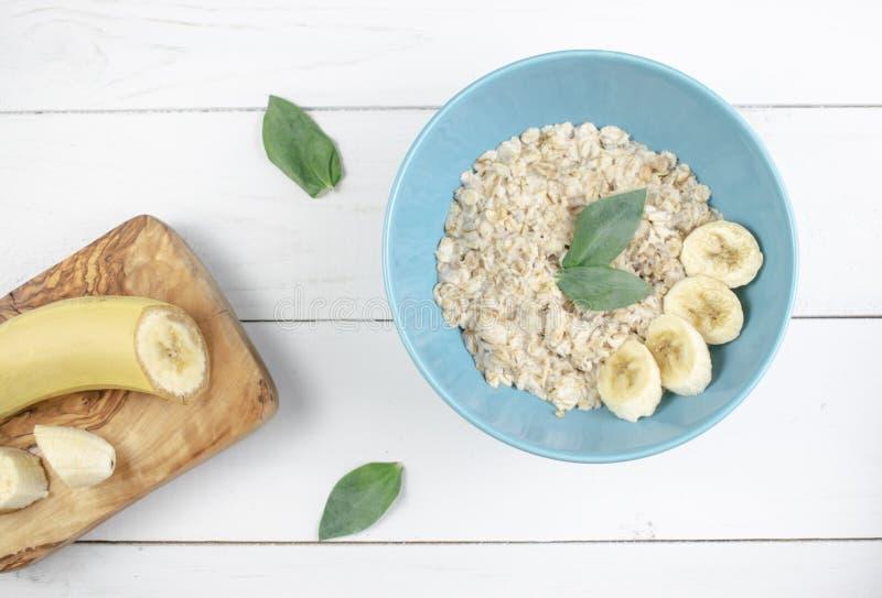 Πιάτο με τις νόστιμες oatmeal και μπανανών φέτες στο άσπρο ξύλινο υπόβαθρο Εικόνα έννοιας του προγεύματος, υγιής κατανάλωση στοκ εικόνες