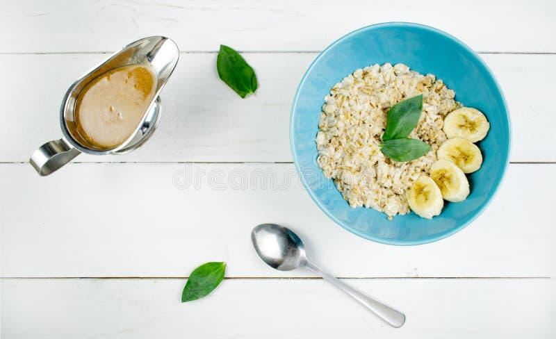 Πιάτο με τις νόστιμες oatmeal και μπανανών φέτες στο άσπρο ξύλινο υπόβαθρο Εικόνα έννοιας του προγεύματος, υγιής κατανάλωση στοκ φωτογραφία με δικαίωμα ελεύθερης χρήσης