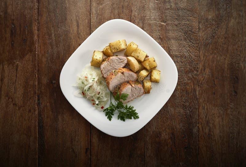 Πιάτο με τις φέτες tenderloin χοιρινού κρέατος, των ψημένων πατατών και του vinaigrette κρεμμυδιών στοκ εικόνες