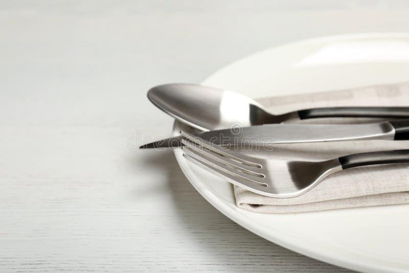 Πιάτο με το δίκρανο, το μαχαίρι και το κουτάλι στον πίνακα στοκ εικόνες