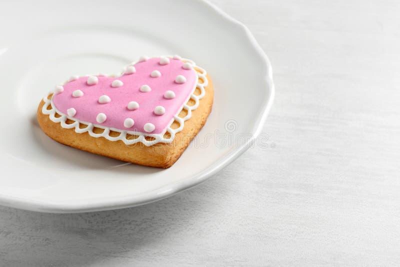 Πιάτο με το διακοσμημένο διαμορφωμένο καρδιά μπισκότο στον ξύλινο πίνακα στοκ φωτογραφία με δικαίωμα ελεύθερης χρήσης