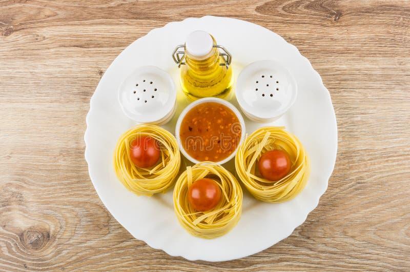 Πιάτο με το φυτικό έλαιο, τα ζυμαρικά tagliatelle, τα καρυκεύματα και τη σάλτσα στοκ φωτογραφία