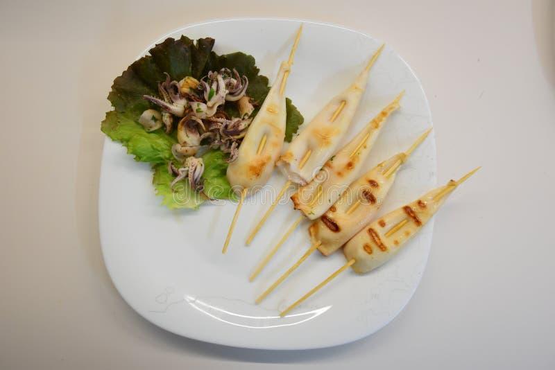 πιάτο με το χταπόδι μωρών στα φύλλα σαλάτας και τα ψημένα στη σχάρα μαλάκια στοκ εικόνες