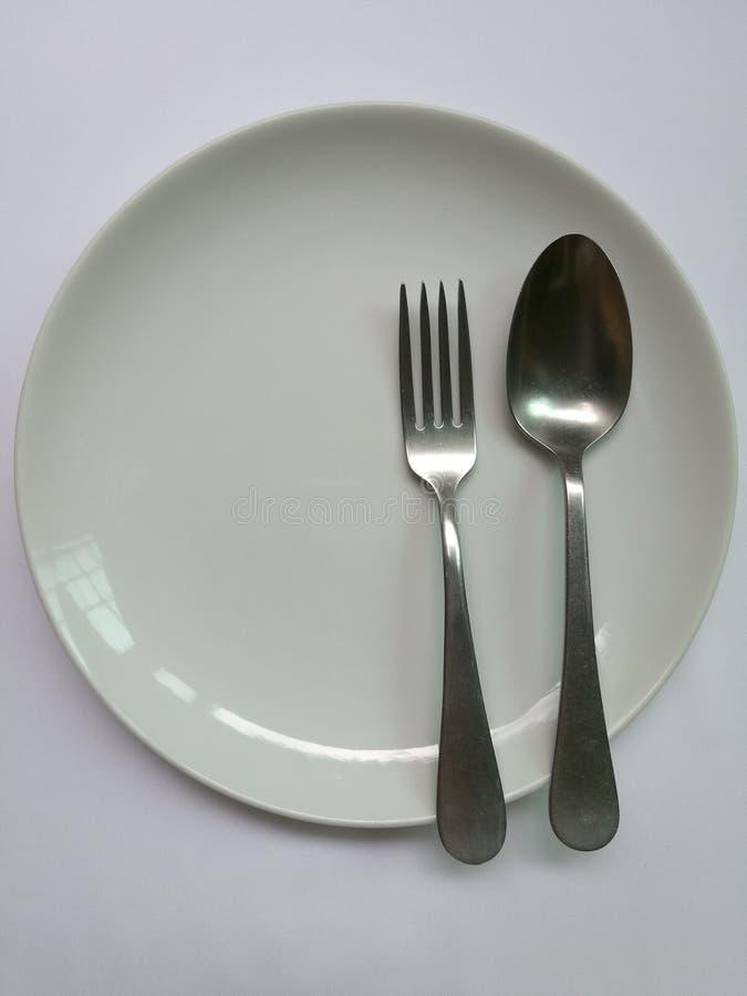 Πιάτο πορσελάνης με το κουτάλι και το δίκρανο στοκ εικόνες με δικαίωμα ελεύθερης χρήσης