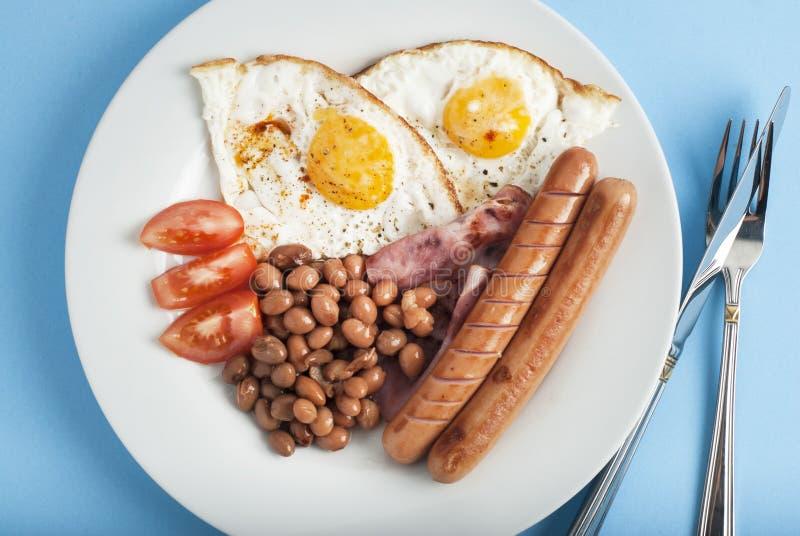 Πιάτο του προγεύματος με τα τηγανισμένα αυγά, φέτες φασολιών μπέϊκον tomatoe στο μπλε υπόβαθρο στοκ εικόνα