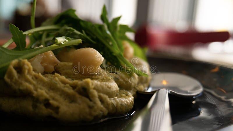 Πιάτο του χαρακτηριστικού λιβανέζικου hummus που καρυκεύεται με τους διάφορους τρόπους στοκ εικόνα