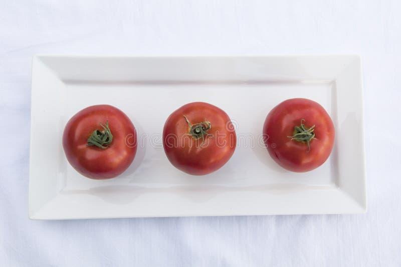 πιάτο τρία ντομάτες στοκ εικόνες