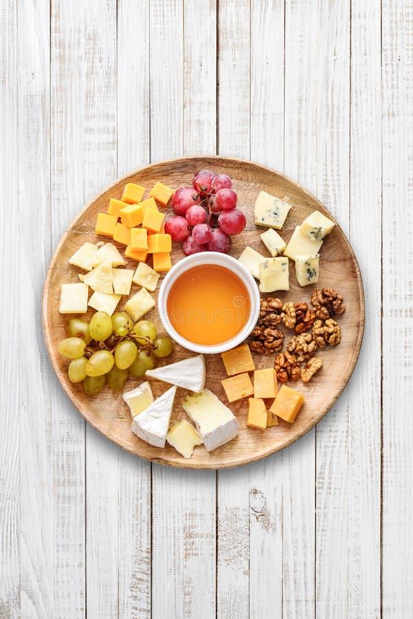 Πιάτο τυριών - διάφοροι τύποι τυριών με το μέλι στοκ φωτογραφία