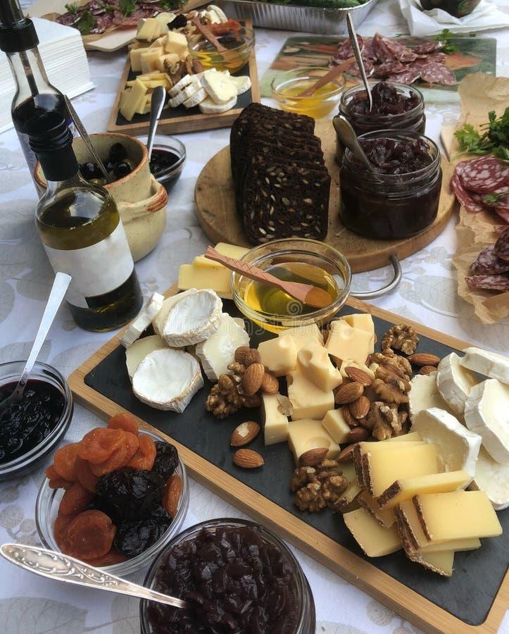Πιάτο τυριών με το moldy τυρί κομματιών, το λουκάνικο, το ελαιόλαδο, τα σύκα, το μέλι και τα καρύδια στοκ εικόνα