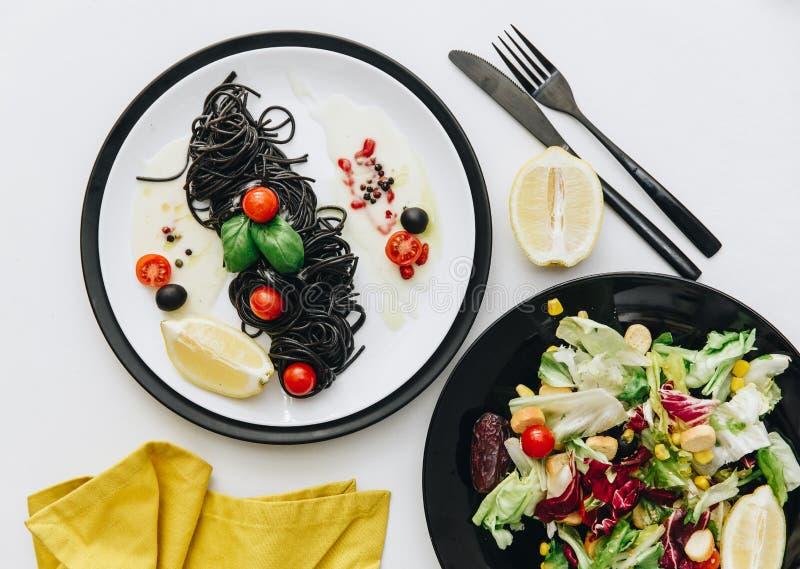 Πιάτο των μαύρων μακαρονιών με το κεράσι ντοματών και τη φρέσκια θερινή σαλάτα Επίπεδος βάλτε στοκ εικόνες