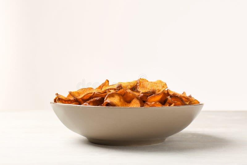 Πιάτο των τσιπ γλυκών πατατών στον πίνακα στο άσπρο κλίμα στοκ εικόνες