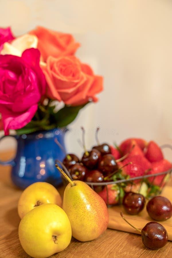 Πιάτο φρούτων στον πίνακα με πολλά τριαντάφυλλα στο μπλε βάζο Selecti στοκ εικόνες