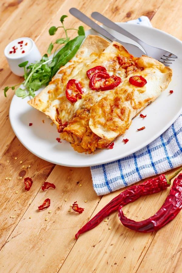 Πιάτο Enchiladas με το κόκκινο - καυτό τσίλι και ξινή κρέμα στοκ εικόνα με δικαίωμα ελεύθερης χρήσης