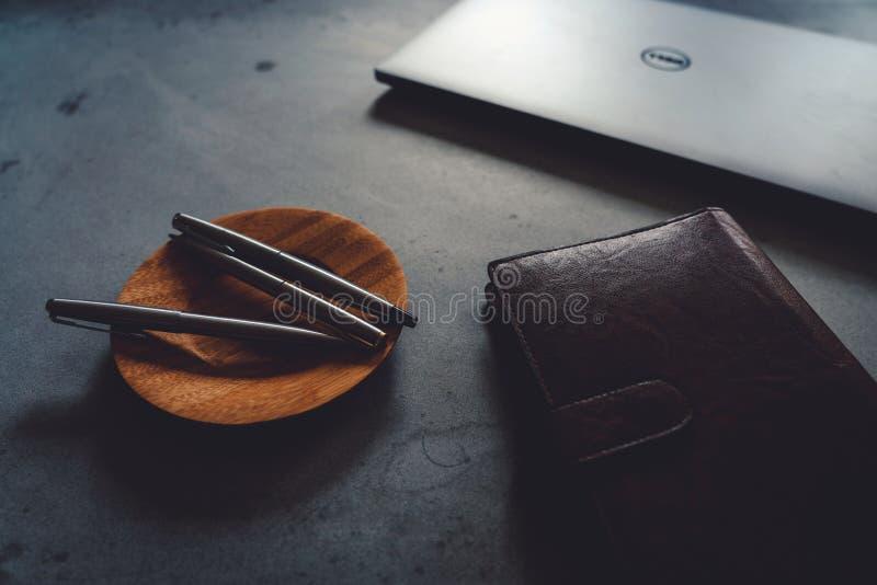 Πιατάκι καφέ, μάνδρες πολυτέλειας, lap-top και σημειωματάριο στο συγκεκριμένο πίνακα στοκ φωτογραφία με δικαίωμα ελεύθερης χρήσης