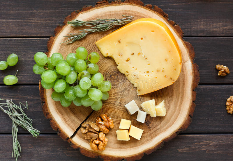 Πιατέλα τυριών, χορτάρι γκούντα σε φυσικό ξύλινο δίσκο με τα σταφύλια και τα καρύδια στοκ φωτογραφία με δικαίωμα ελεύθερης χρήσης