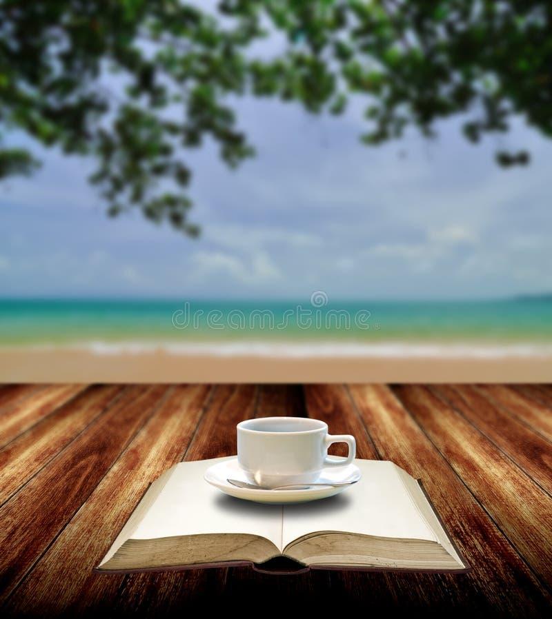 Πιείτε τον καφέ και διαβάστε το βιβλίο στην παραλία στοκ φωτογραφία με δικαίωμα ελεύθερης χρήσης