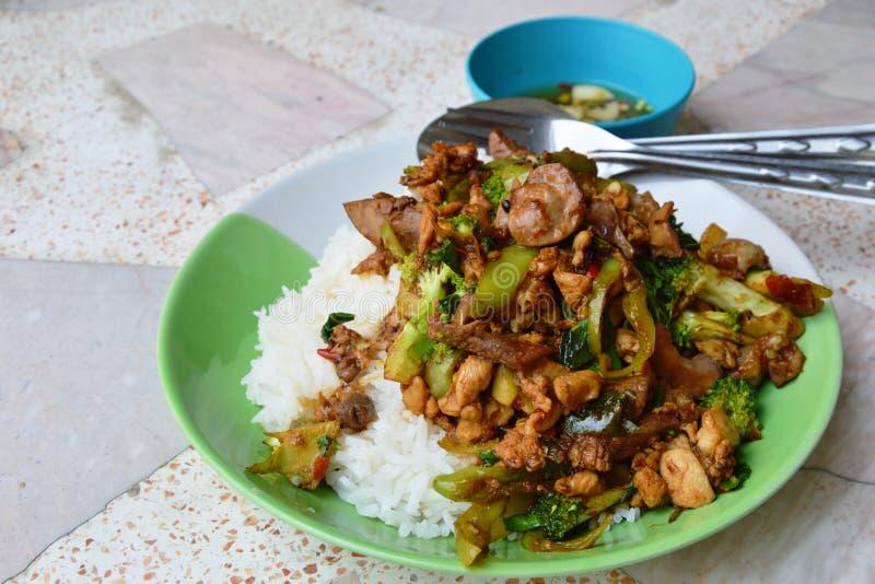 Πικάντικα ανακατώνω-τηγανισμένα innards κοτόπουλου με τα φύλλα βασιλικού στο ρύζι στοκ φωτογραφία με δικαίωμα ελεύθερης χρήσης