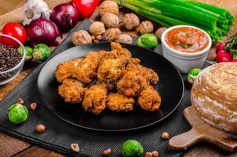 Πικάντικα πασπαλισμένα με ψίχουλα φτερά κοτόπουλου με το σπιτικό ψωμί στοκ εικόνα