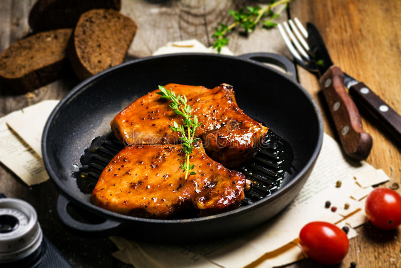 Πικάντικες ψημένες στη σχάρα μπριζόλες χοιρινού κρέατος στο skillet στοκ φωτογραφία με δικαίωμα ελεύθερης χρήσης
