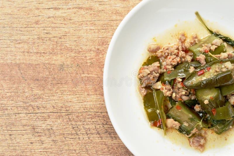 Πικάντικος ανακατώστε την τηγανισμένη μελιτζάνα φετών με το κομματιασμένο φύλλο χοιρινού κρέατος και βασιλικού στο πιάτο στοκ φωτογραφία με δικαίωμα ελεύθερης χρήσης