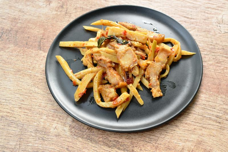Πικάντικος ανακατώστε τον τηγανισμένο βλαστό μπαμπού με το τριζάτο κάρρυ χοιρινού κρέατος στο πιάτο στοκ εικόνες