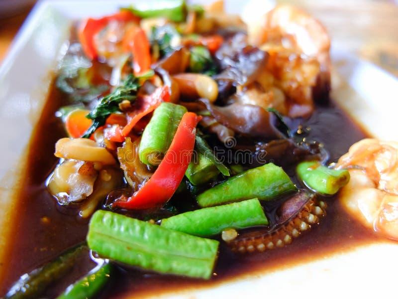 Πικάντικος τηγανισμένος θαλασσινά βασιλικός στο άσπρο πιάτο στοκ εικόνες