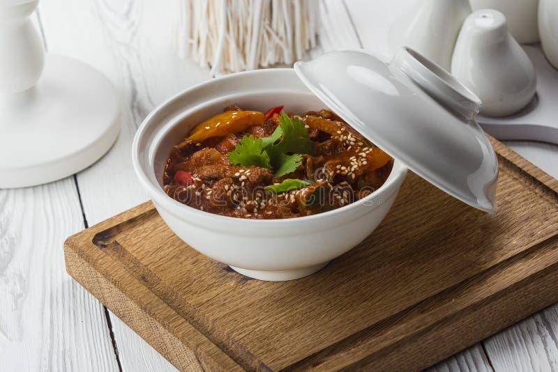 Πικάντικο κοτόπουλο με τους σπόρους σουσαμιού σε ένα κύπελλο στοκ εικόνα