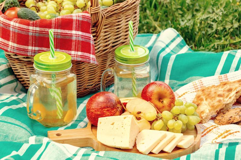 Πικ-νίκ στη χλόη μια θερινή ημέρα - καλάθι, σταφύλια, τυρί, ψωμί, μήλα - μια έννοια της θερινής υπαίθριας αναψυχής στοκ εικόνες
