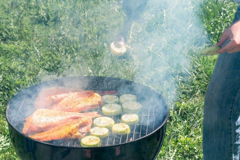 Πικ-νίκ υπαίθρια το καλοκαίρι Μαγείρεμα σε μια στρογγυλή πέρκα θάλασσας ψαριών σχαρών και τις φέτες κολοκυθιών στοκ φωτογραφία με δικαίωμα ελεύθερης χρήσης