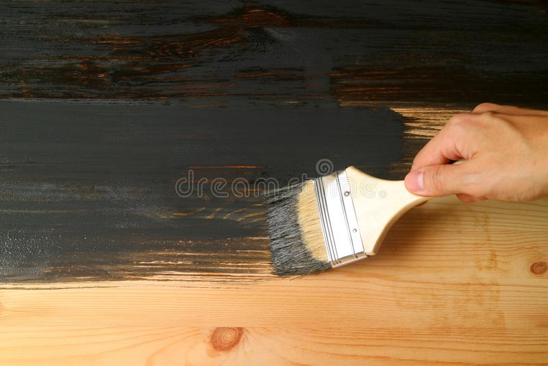 Πινέλο εκμετάλλευσης χεριών που χρωματίζει την επιφάνεια των ξύλινων επίπλων με το σκοτεινό γκρίζο χρώμα στοκ φωτογραφίες με δικαίωμα ελεύθερης χρήσης