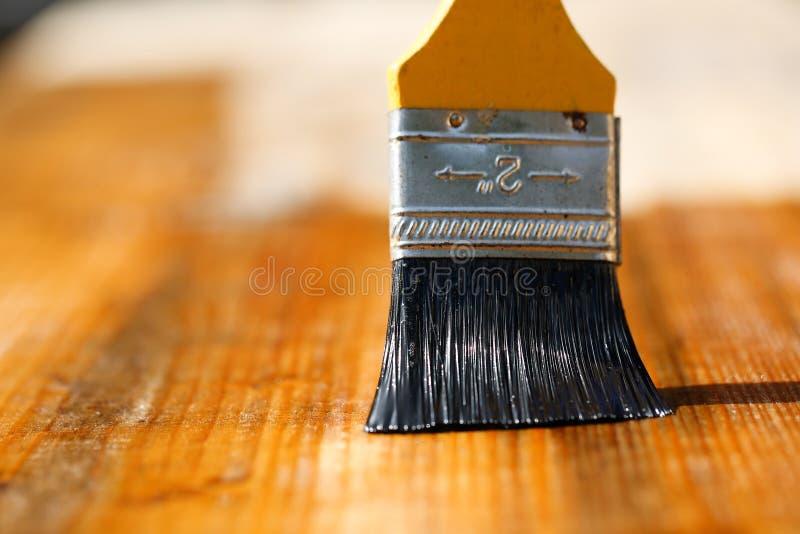 Πινέλο που γλιστρά πέρα από την ξύλινη επιφάνεια, που προστατεύει το ξύλο στοκ εικόνες