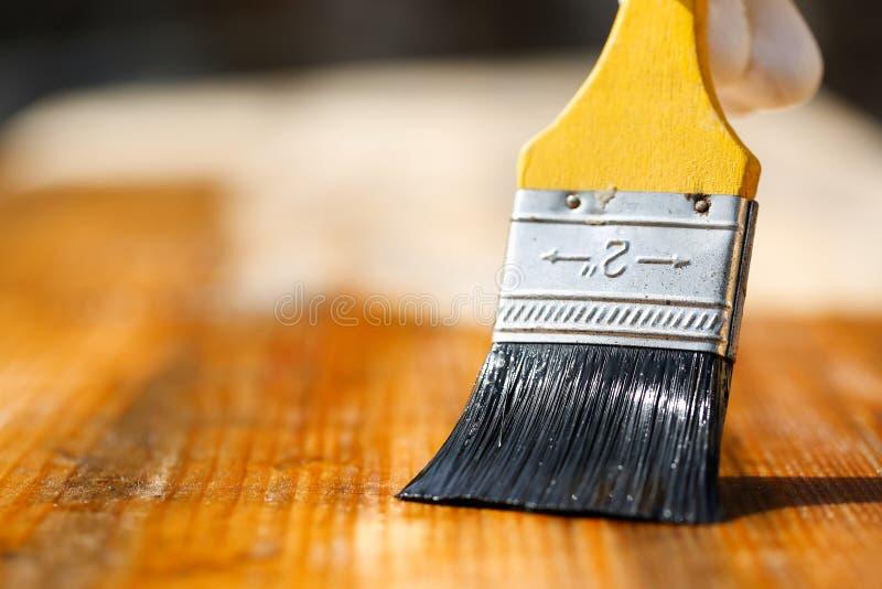Πινέλο που γλιστρά πέρα από την ξύλινη επιφάνεια, που προστατεύει το ξύλο στοκ εικόνα